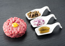 Beef tartare on black chalkboard Royalty Free Stock Image
