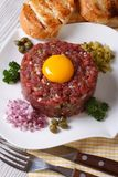 Beef tartare close up on a white plate. vertical top view. Beef tartare with egg close up on a white plate. vertical top view Royalty Free Stock Photo