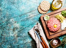 Beef tartare on cutting board. With pickled cucumber and fresh onions on blue background, top view with copy space Royalty Free Stock Photos