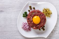 Beef tartare with egg close up on the table. top view Stock Photos