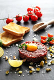 Beef tartare with egg yolk. On a black wooden table Stock Photos