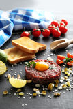 Beef tartare with egg yolk. On a black wooden table Royalty Free Stock Photo