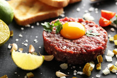 Beef tartare with egg yolk. On a black wooden table Stock Images