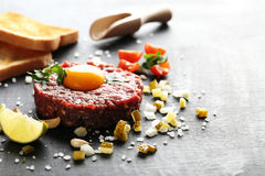 Beef tartare. With egg yolk on a black wooden table Royalty Free Stock Images