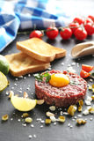 Beef tartare. With egg yolk on a black wooden table Royalty Free Stock Image