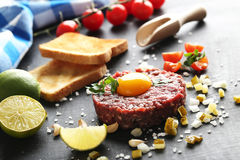 Beef tartare. With egg yolk on a black wooden table Stock Photography