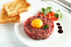 Beef tartare with egg yolk. On a blue wooden table Royalty Free Stock Photography