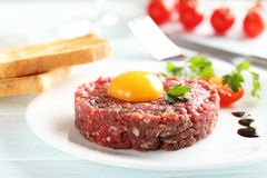 Beef tartare with egg yolk. On a blue wooden table Stock Photos