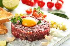 Beef tartare with egg yolk. On a blue wooden table Stock Photography