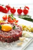 Beef tartare with egg yolk. On a blue wooden table Royalty Free Stock Image