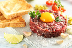 Beef tartare with egg yolk. On a blue wooden table Royalty Free Stock Photo