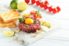 Beef tartare with egg yolk. On a blue wooden table Royalty Free Stock Photos