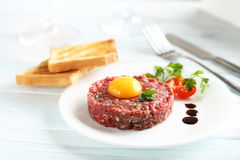 Beef tartare. With egg yolk on a blue wooden table Stock Photos