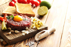 Beef tartare with egg yolk. On a brown wooden table Stock Photos