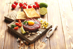 Beef tartare. With egg yolk on a brown wooden table Stock Photo