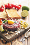 Beef tartare. With egg yolk on a brown wooden table Royalty Free Stock Image