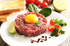 Beef tartare with egg yolk. On a grey wooden table Royalty Free Stock Photography