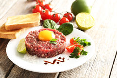 Beef tartare with egg yolk. On a grey wooden table Stock Photo