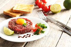 Beef tartare with egg yolk. On a grey wooden table Stock Image