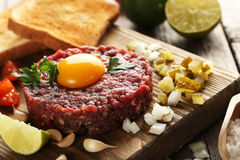 Beef tartare with egg yolk. On a grey wooden table Royalty Free Stock Photos