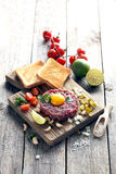 Beef tartare. With egg yolk on a grey wooden table Royalty Free Stock Photo