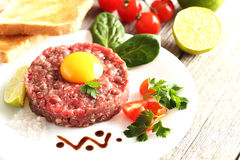 Beef tartare. With egg yolk on a grey wooden table Royalty Free Stock Photography