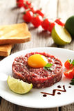 Beef tartare. With egg yolk on a grey wooden table Royalty Free Stock Photos