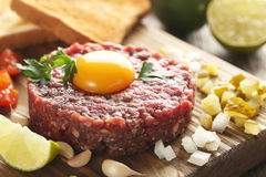 Beef tartare. With egg yolk on a grey wooden table Stock Image