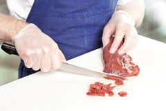 Beef tartare preparation. On white board with big knife Stock Photo