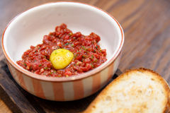 Beef tartare with quail egg and rustic bread.  Royalty Free Stock Photos