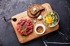 Beef tartare. With salad and garlic toasts on dark marble background Stock Image