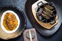 Beef tenderloin steak grilled with a side dish of baked batata, black background. royalty free stock photos
