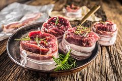 Beef tenderloin steak wrapped in bacon stored into the pan.  royalty free stock images
