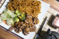 Beef Teriyaki with noodles on a white plate stock image