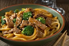 Beef Teriyaki with Udon Noodles. A bowl of delicious beef teriyaki with broccoli, udon noodles and sesame seed garnish Royalty Free Stock Images