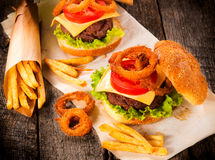 Beef time. Big beef burger with onion rings and french fries.Selective focus on the burger Royalty Free Stock Photo