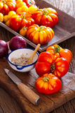 Beef tomatoes, salt bowl with spoon and a knife Royalty Free Stock Images