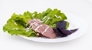 Beef tongue with appetizing herbs. Lettuce and basil Royalty Free Stock Photography