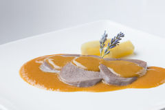 Beef tongue spanish traditional cuisine with wine sauce. Delicious recipe from spain cow meat boiled on a white plate Royalty Free Stock Photo