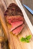 Beef Top Sirloin Steak Roast Sliced Coooked Medium Rare. A large piece of grilled top sirloin sits on cutting board sliced and peppered Royalty Free Stock Photo