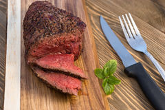 Beef Top Sirloin Steak Roast Sliced Coooked Medium Rare. A large piece of grilled top sirloin sits on cutting board sliced and peppered Stock Photos