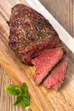 Beef Top Sirloin Steak Roast Sliced Coooked Medium Rare. A large piece of grilled top sirloin sits on cutting board sliced and peppered Royalty Free Stock Image