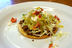 Beef Tostada. Traditional, Mexican Beef Tostada with lettuce, shredded cheese, tomatoes, and queso fresco Stock Photo