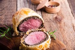 Beef Wellington, classic steak dish on cutting board. Beef Wellington, classic steak dish on rustic wooden table ready to eat Stock Photos