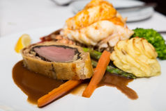 Beef Wellington Lobster Tail and Potatoes Stock Photos