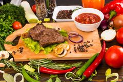 Beef on Wood Cutting Board with Salsa and Veggies Royalty Free Stock Photos
