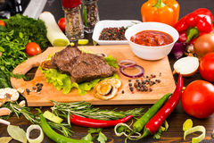 Beef on Wood Cutting Board with Salsa and Veggies Stock Image