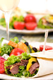 Beef Wrap. A appetizing beef steak wrap with lots of vegetables and a side salad Royalty Free Stock Photos