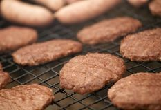 BEEFBURGERS AND SAUSAGES ON BARBECUE. BEEFBURGERS AND SAUSAGES COOKING ON BARBECUE IN CLOSE UP Royalty Free Stock Photography