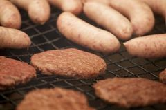 BEEFBURGERS AND SAUSAGES ON BARBECUE. BEEFBURGERS AND SAUSAGES COOKING ON BARBECUE IN CLOSE UP Stock Photography
